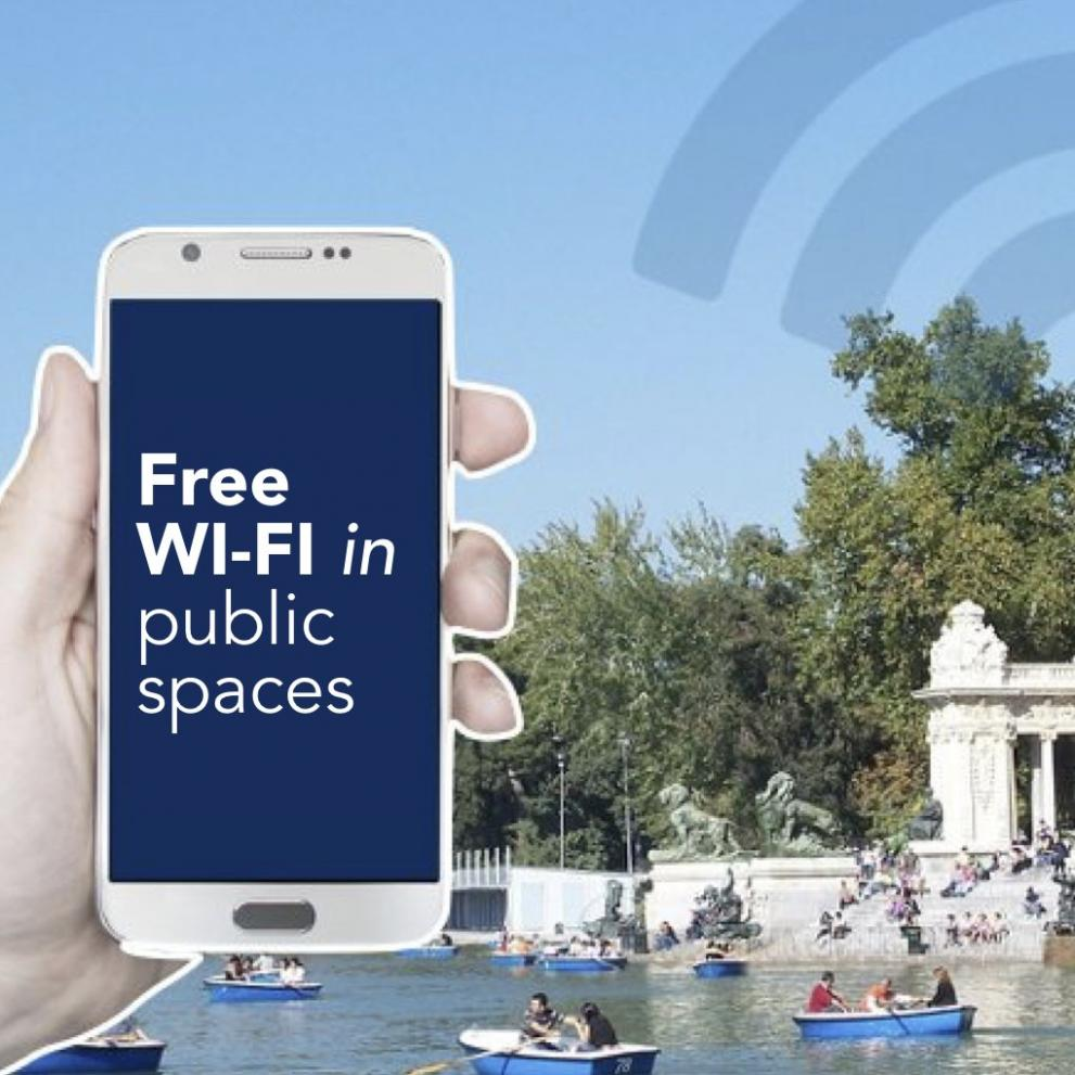 """Handing holding smart phone with text """"Free Wifi in public spaces"""""""